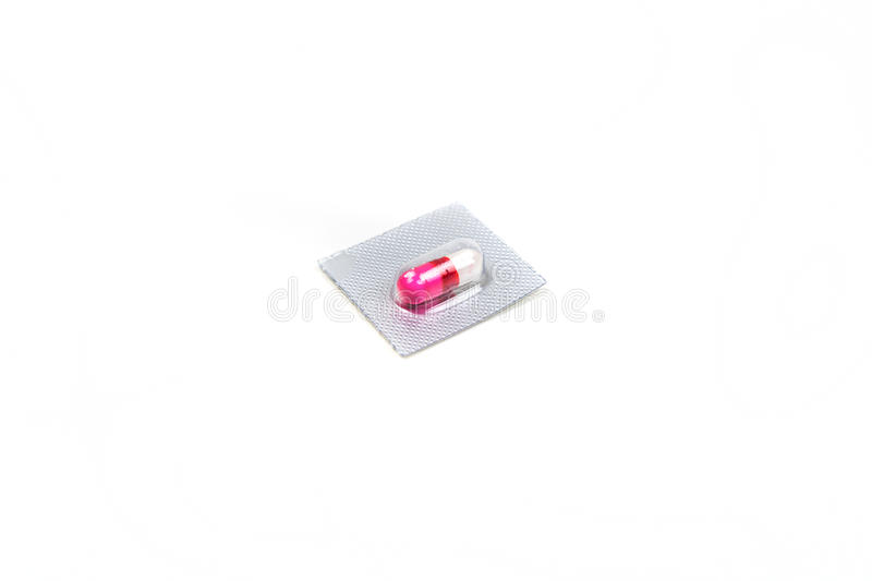 Single pink and white pill in a blister pack. Isolated on white background stock photo