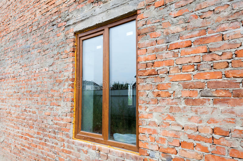 Single plastic window on a wall with red bricks. nstall window against brick wall facade stock photo
