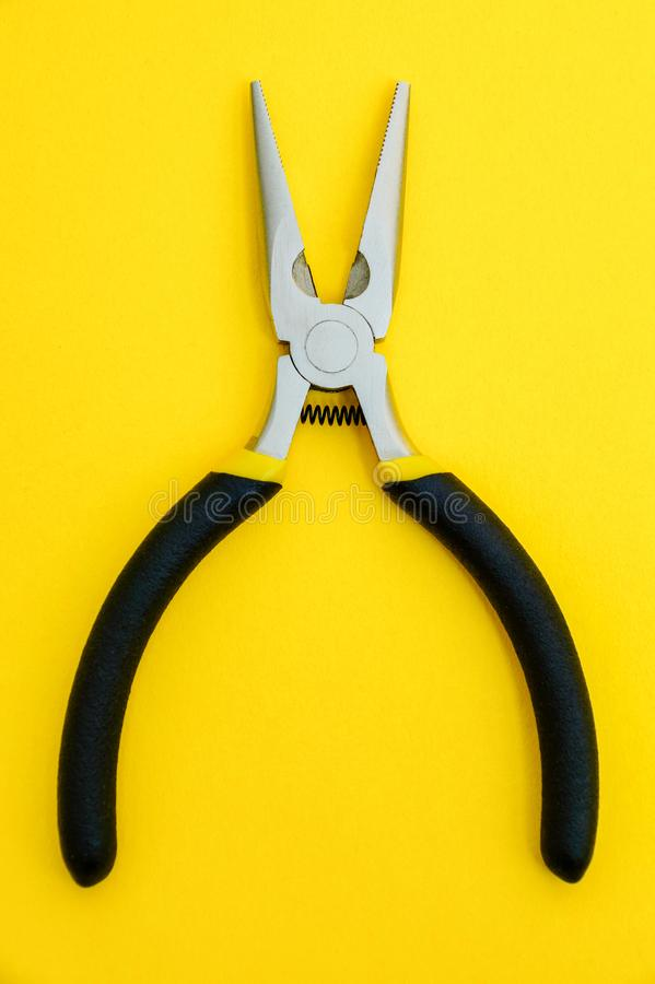 Single pliers tool with rubber handles for the master electrician on yellow background stock photos