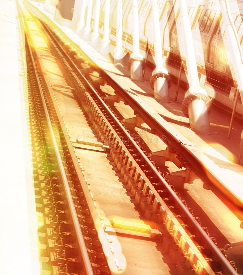 Single point perspective image of burning metro rails and suspenders of a bridge in a dizzy look. stock photo