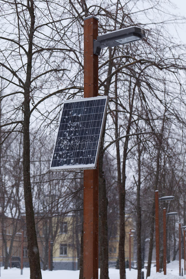 Single power plant at winter. One small solar battery, which provides electricity not only for lamp, but for sockets on post's base. Check summer version of it royalty free stock photo