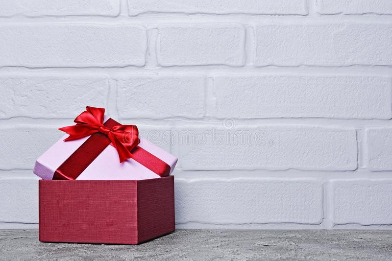 Single purple classic gift box with red satin bow and copy space stock photography