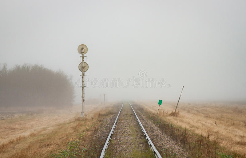 Single Railroad Track Receding into Fog. A pair of rails recede into the distant prairie fog stock photography