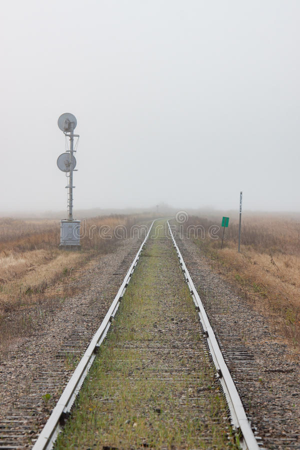 Single Railroad Track Receding into Fog. A pair of rails recede into the distant prairie fog royalty free stock images