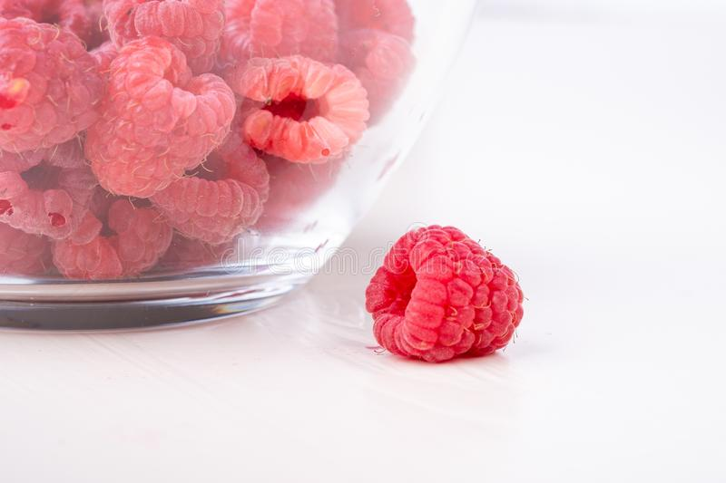 Single raspberry close to transparent glass plate with raspberries  tasty sweet bright on white background copy space macro stock photography