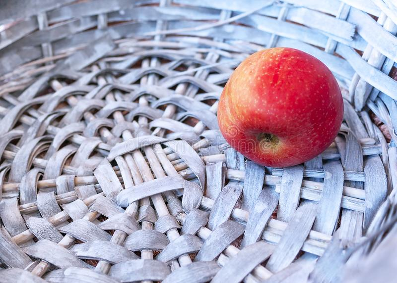 Single Red Apple in a Gray Wicker Basket. Copy Space.  royalty free stock photography