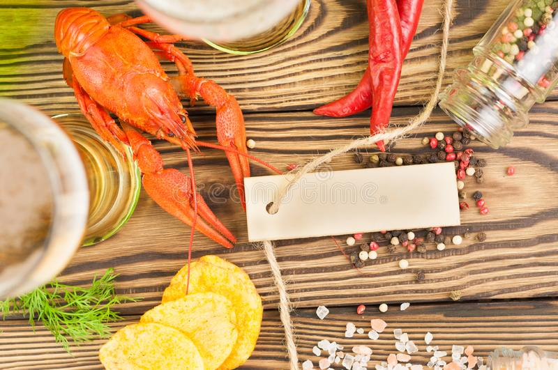 Single red boiled crayfish near glasses of beer and fresh green dill and potato chips and scattered pepper and salt and red hot pe. Pper and blank rectangle royalty free stock image