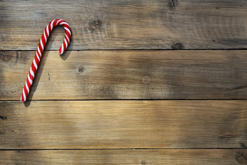 Single red candy cane on a brown rustic plank royalty free stock photos