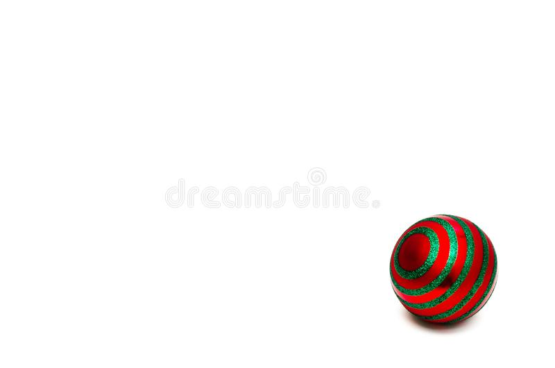 Single red christmas ball with green circular stripes on a white background. Minimal Christmas holiday composition stock photography