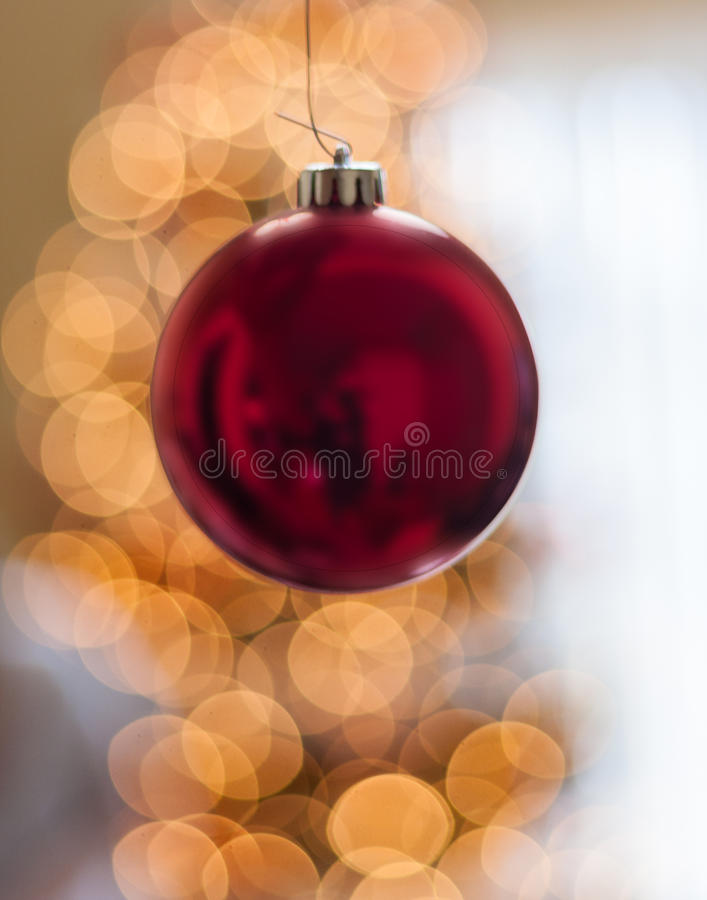 Single Red Christmas Ornament hanging in front of lights stock image