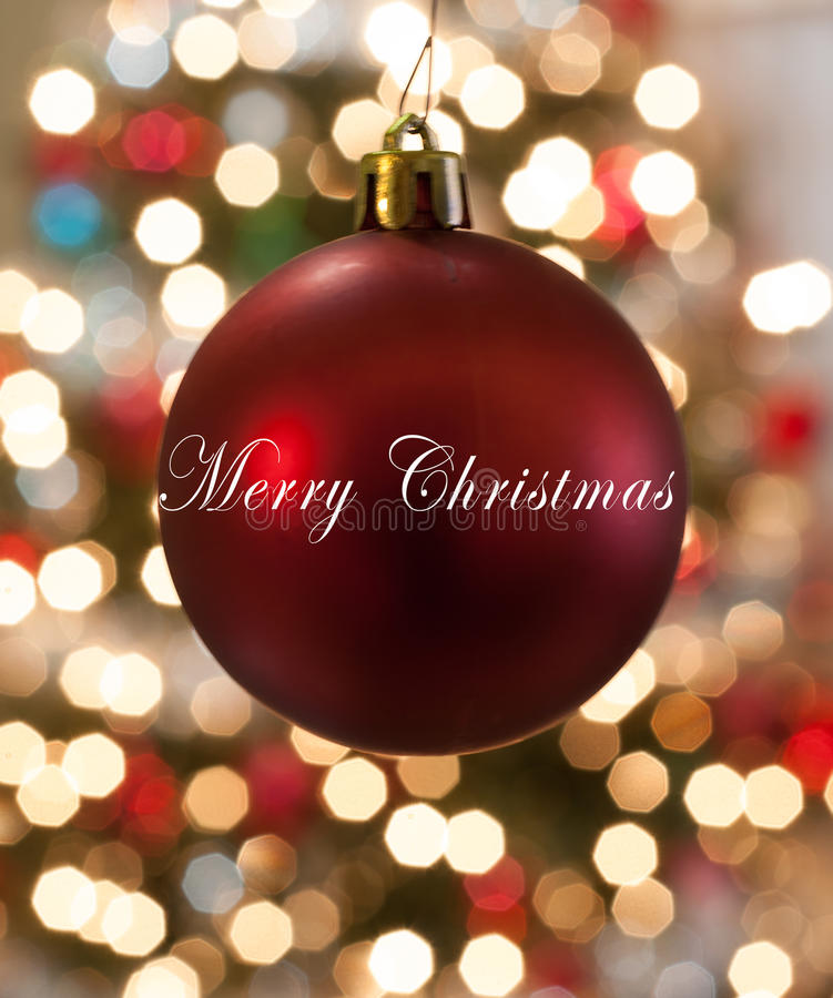 Single Red Christmas Ornament hanging in front of lights stock photo