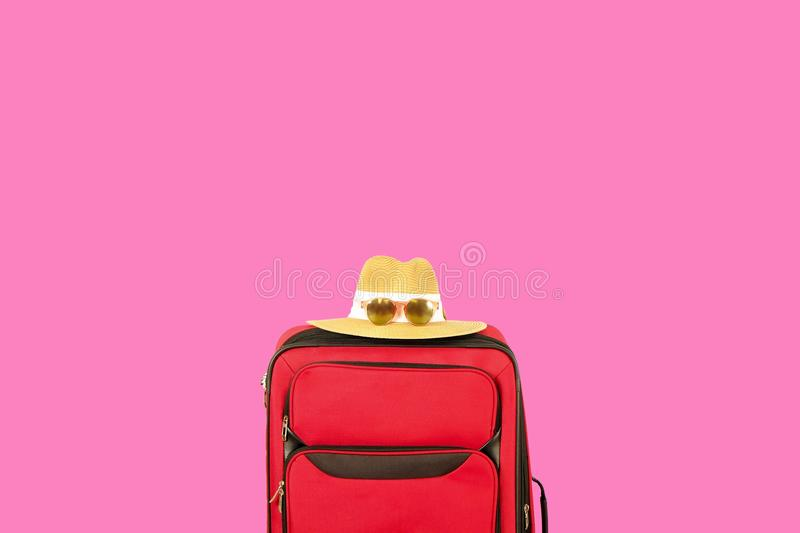 Single red durable textile luggage with women`s straw hat, sunglasses. One suitcase prepared for business trip. Traveling alone c. Oncept. bright pink background stock images
