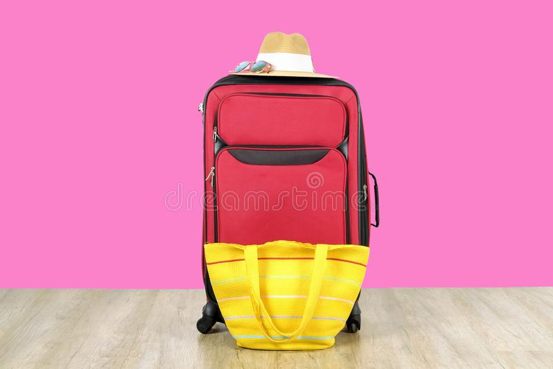 Single red durable textile luggage with women`s straw hat, sunglasses, yellow beach bag. One packed suitcase. Traveling alone con. Cept. Bright pink background stock photos