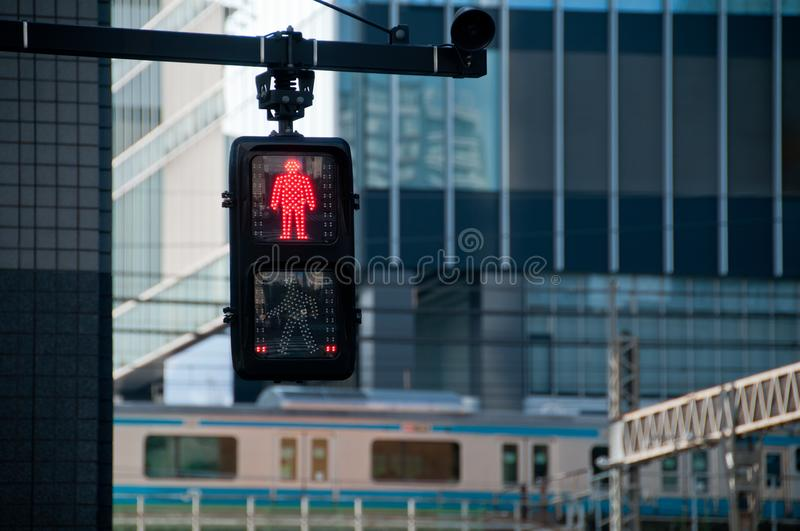 Single Red man stop traffic sign in front of Tokyo train station royalty free stock photography