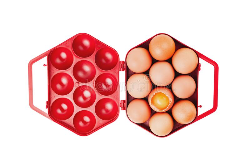 Single red plastic box full of set of whole and one broken fresh egg isolated on white background. Top view stock photography