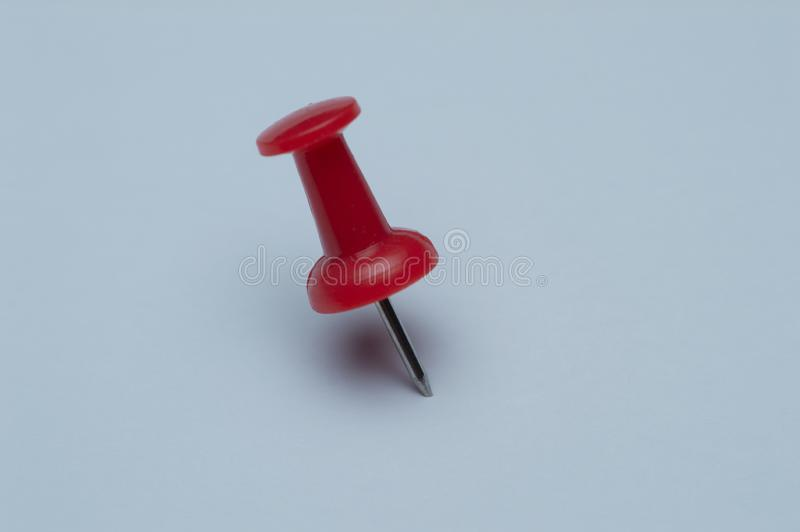 Single red pushpin isolated on white papers stock image