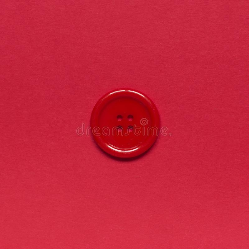 Single red sewing button on red background.  stock photos