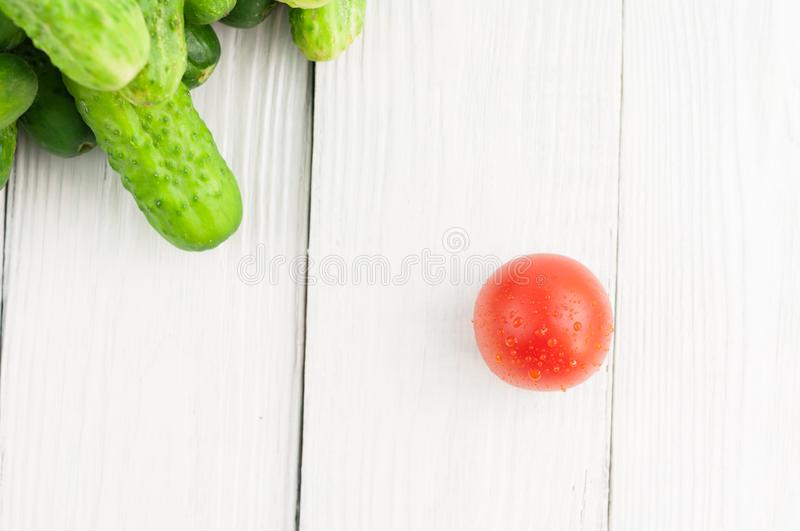 Single red tomato and heap of green fresh cucumbers on rustic background. Single red tomato and heap of green fresh cucumbers on white rustic background royalty free stock photography