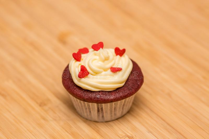 Single red velvet cupcake decorated with buttercream. Handmade red velvet cupcake decorated with buttercream and heart shape candy. Set atop of a wooden board royalty free stock photo