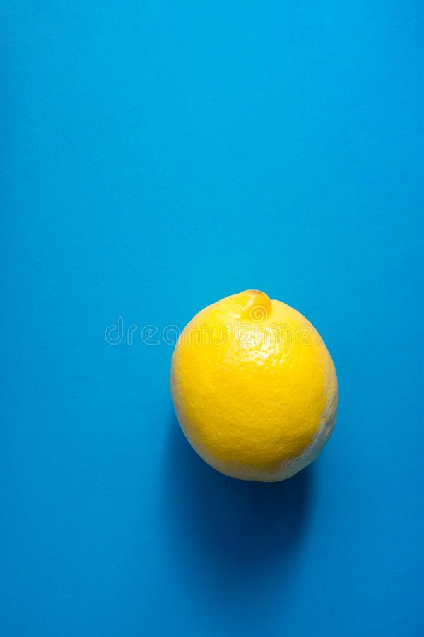 Single Ripe Juicy Whole Lemon on Blue Background. Vitamins Healthy Diet Summer Superfoods. Concept. Food Poster Banner Template. Copy Space Flat Lay stock image