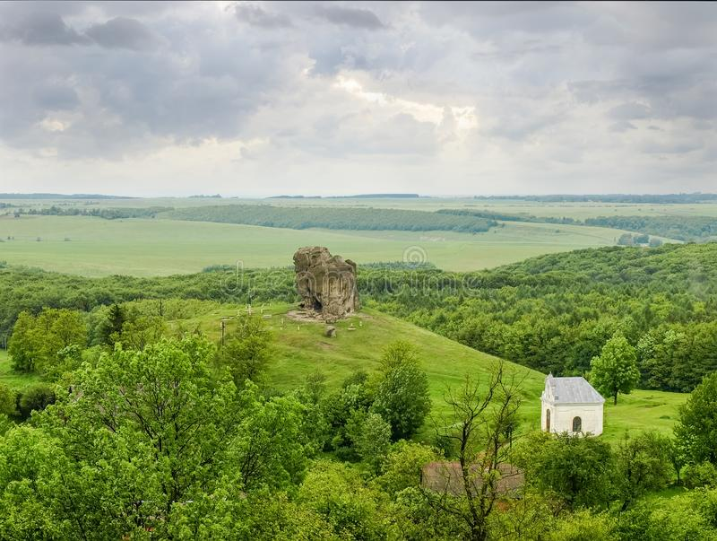 Single rock on hill in Pidkamin, Lviv Oblast, Ukraine. Single rock on hill with chapel on a foreground in a spring cloudy day. Geological monument of nature royalty free stock images