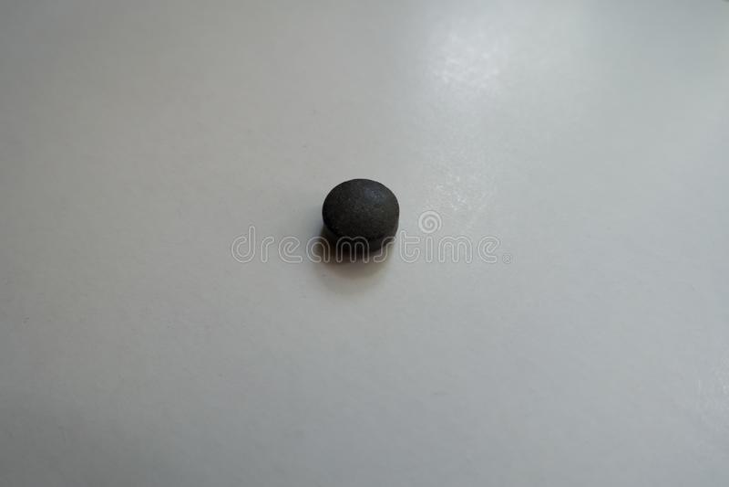 Single black pill of chelated iron. Single round black pill of chelated iron royalty free stock images