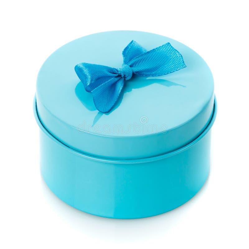 Single round turquoise gift box with blue bow. On white background royalty free stock image