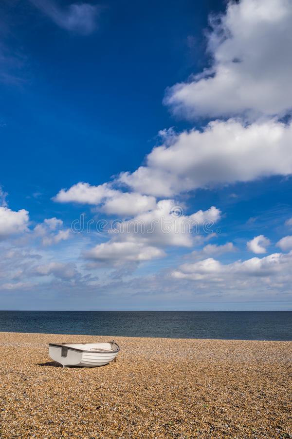 Single rowing boat ona shingle beach facing out to sea. On a bright sunny summers day royalty free stock photo