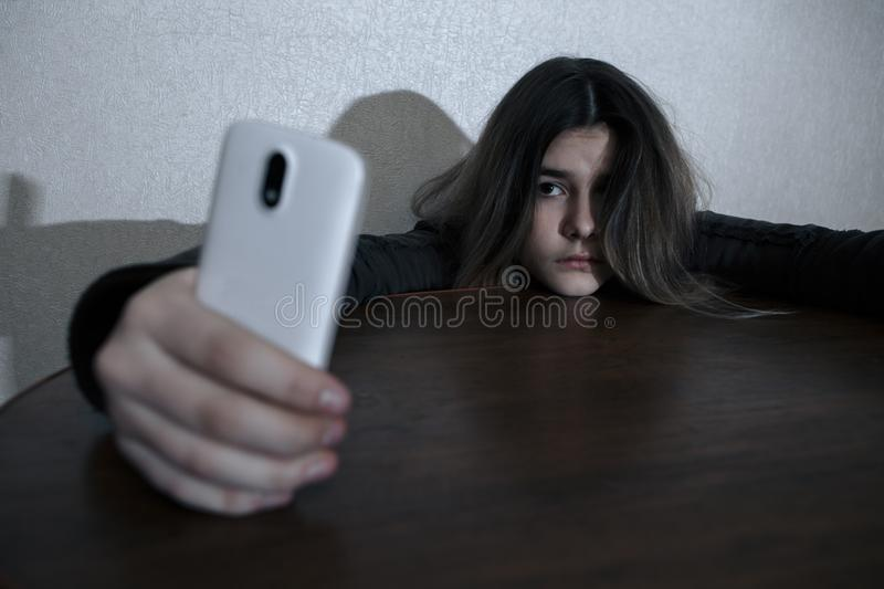Single sad teen holding a mobile phone lamenting sitting on the bed in her bedroom with a dark light royalty free stock images