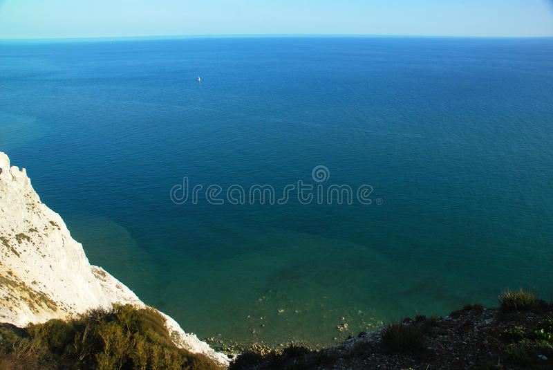 A single sail on the sea, South England cliffs, UK royalty free stock photo