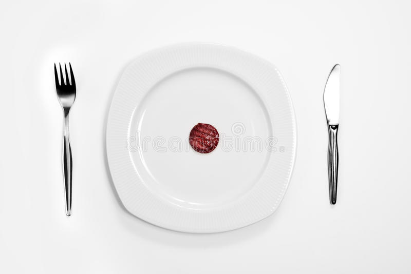 Single sausage. The middle of a plate, knife and fork royalty free stock images