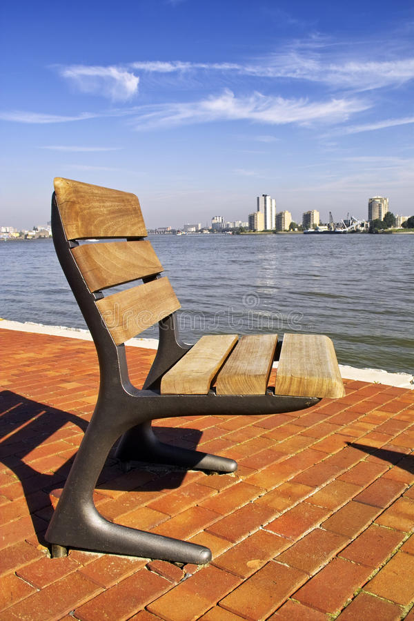 A single seat on the river bank in Rotterdam. Holland royalty free stock photos