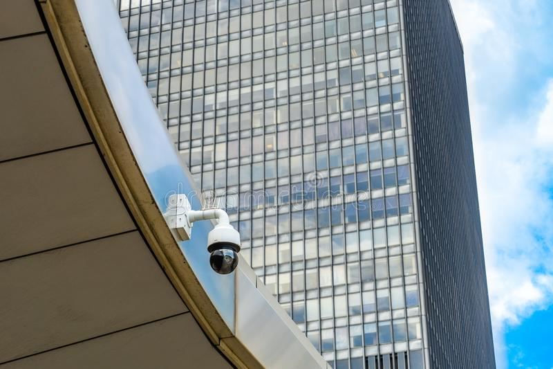 Single Security Camera on facade of contemporary business skyscraper on sunny summer day, security camera on metal beam stock photo