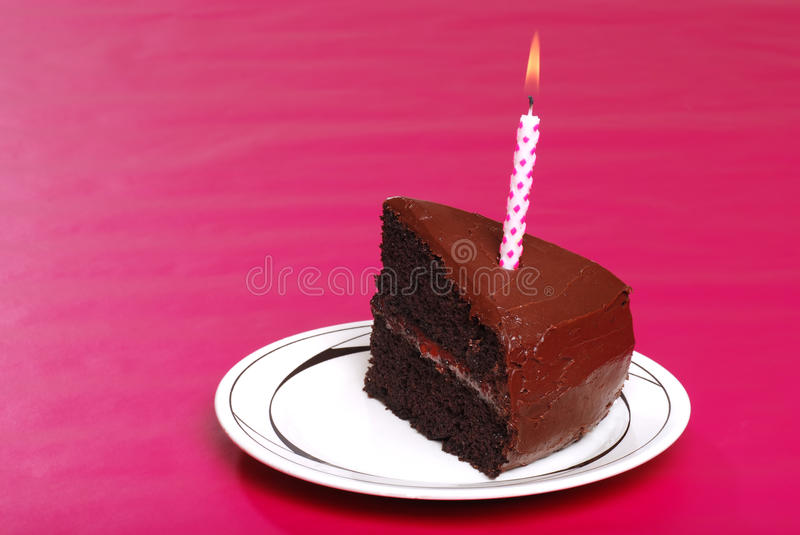 Single serving of birthday cake with candle. On pink background stock photography