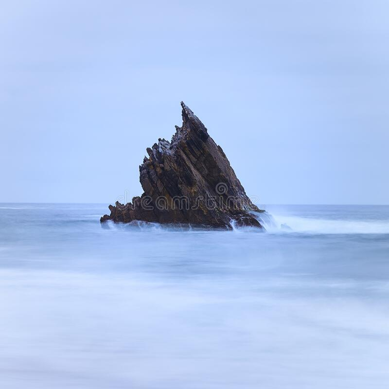 Single sharp rock on the middle of the sea. Long exposure of a single sharp rock on the middle of the sea on a mood day royalty free stock photography