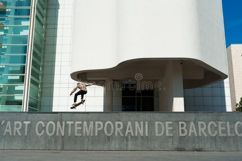 Single skater boy doing tricks in urban city during sunny day in front of modern architecture building royalty free stock photo