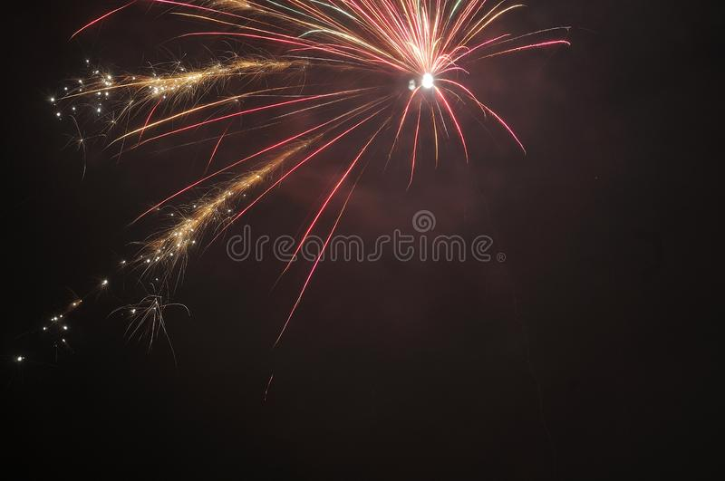 Single skyrocket exploding in dark sky. Single skyrocket exploding on night sky in red and golden sparkling colors stock photos