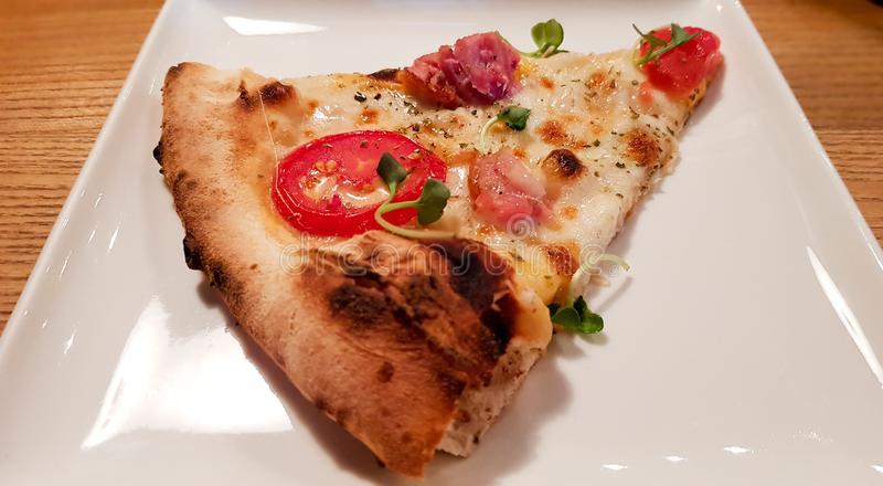 A single slice of cheese pizza on a white plate stock photo