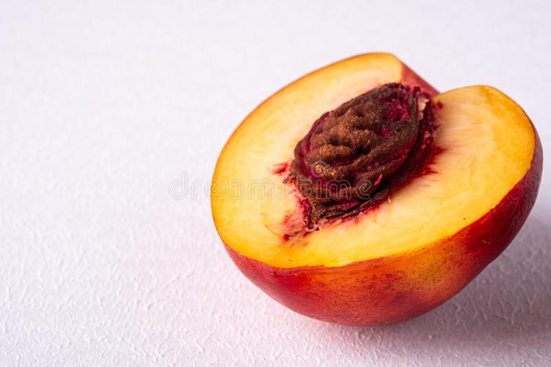 Single slice of peach nectarine fruit with seed on white background, copy space, angle view. Close up royalty free stock photos
