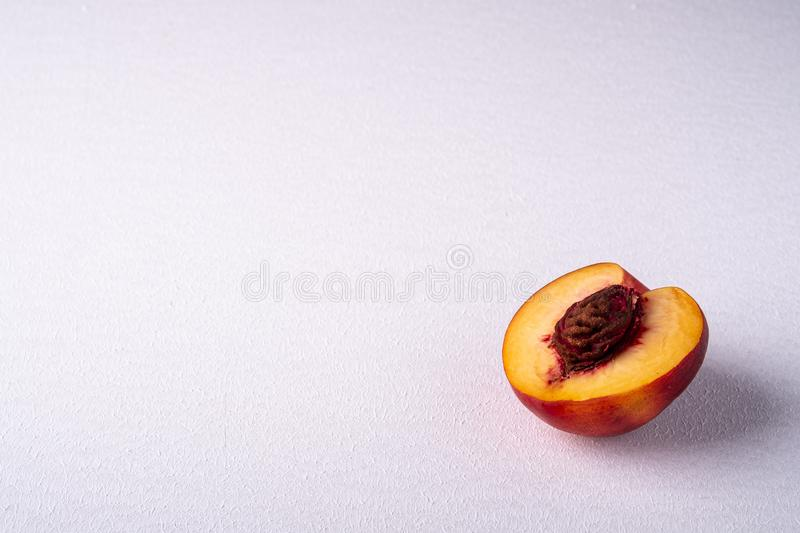 Single slice of peach nectarine fruit with seed on white background, copy space, angle view. Close up royalty free stock photo