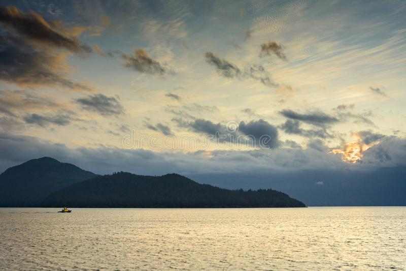 Single small boat, and mountain silhouettes, Howe Sound near Vancouver, Canada royalty free stock photography