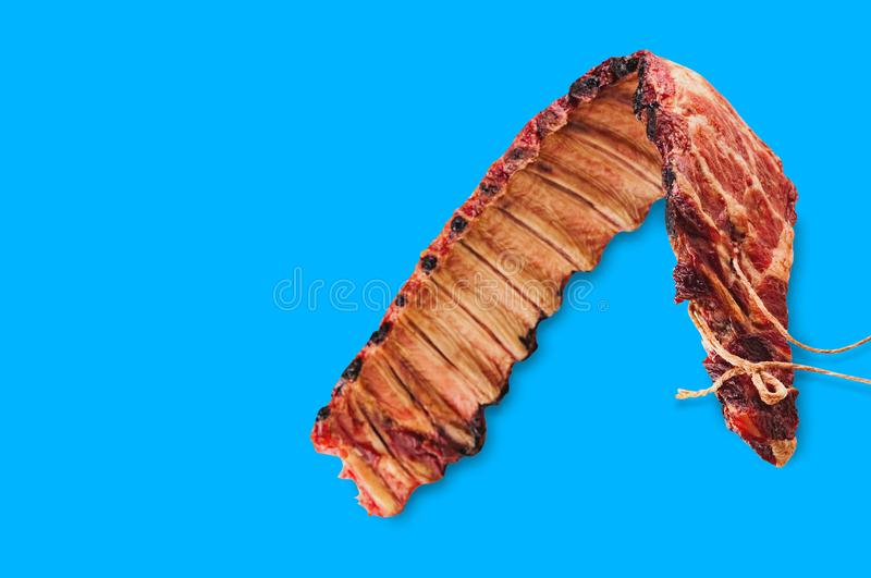 Single smoked ribs of pork on blue background. With copy space for your text royalty free stock photos