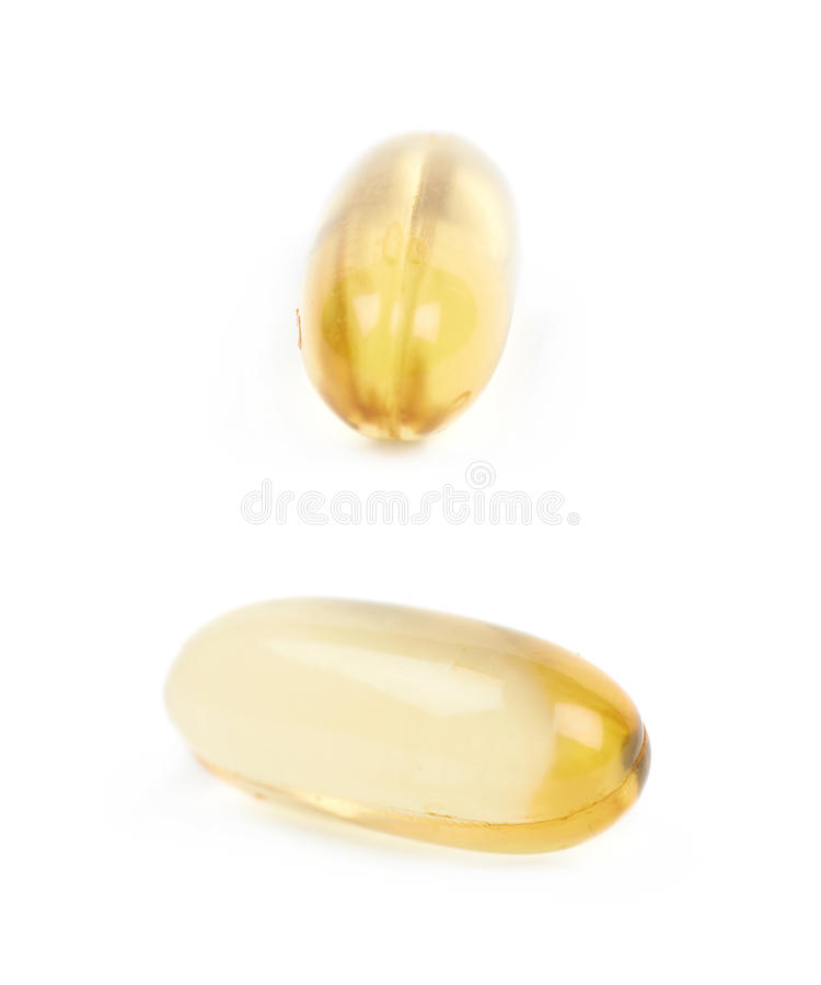 Single softgel pill isolated. Single yellow softgel pill isolated over the white background, set of two different foreshortenings royalty free stock photos