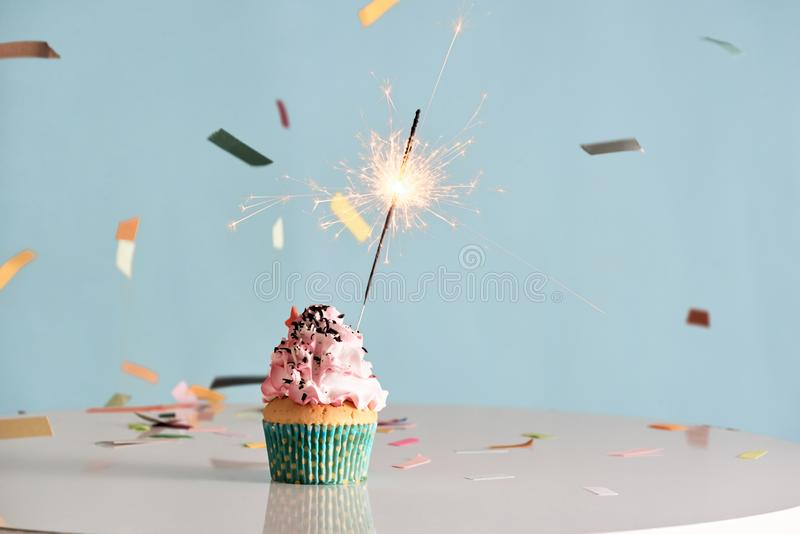 Single sparkler on cupcake blue wall. stock images