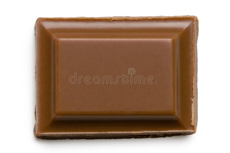 Single square of milk chocolate isolated on white from above stock photos