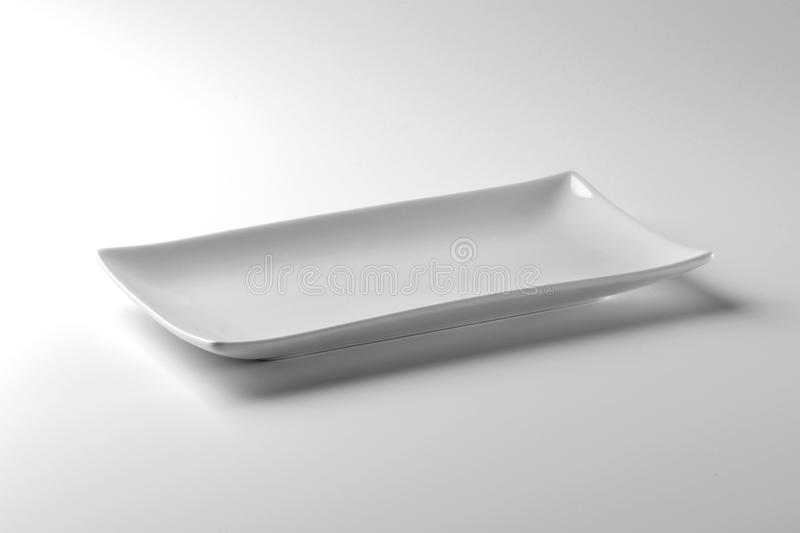 Single Square white plate on white table royalty free stock photo