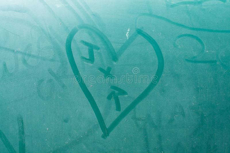 J + R Heart on Old School Aqua Nash. Single stage aqua paint with years of writing on an old abandoned aqua Nash stock images