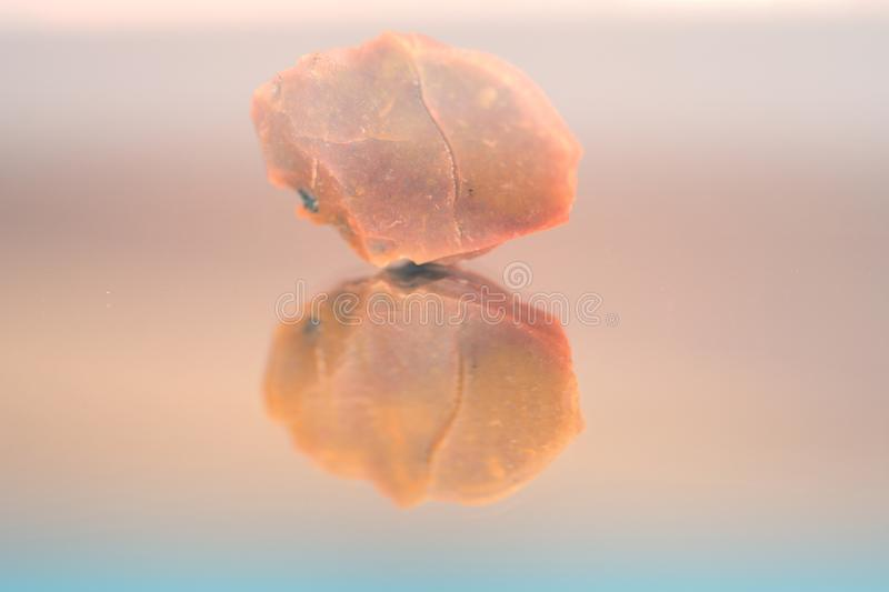 Single stone reflection. Stone reflection in a mirror stock photo