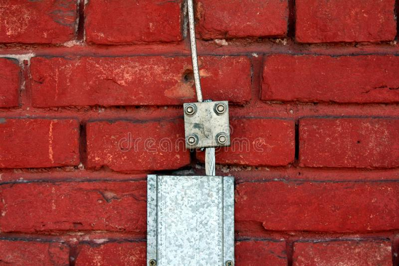 Metal wires used as lightning conductor protection system mounted on red brick wall. Single strong metal wire used as lightning conductor protection system stock images