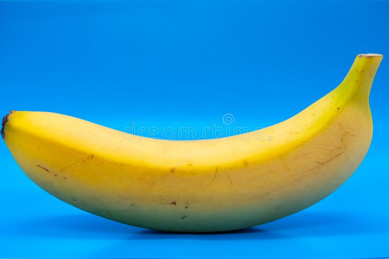 Single sweet banana against light blue background stock photo